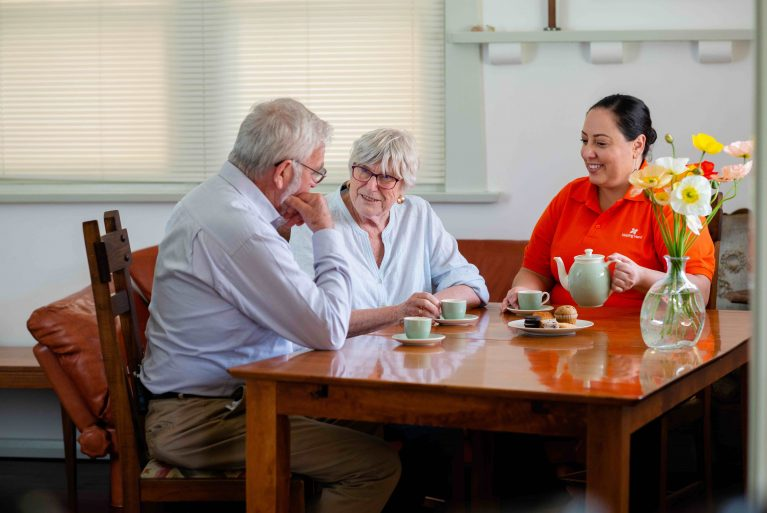A Helping Hand Care worker in bright orange top sits at a table drinking tea with an older couple, Richard and Jolanta