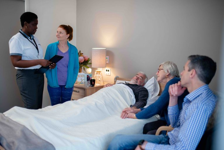 A man is in a bed in a nursing home surrounded by his family and a doctor