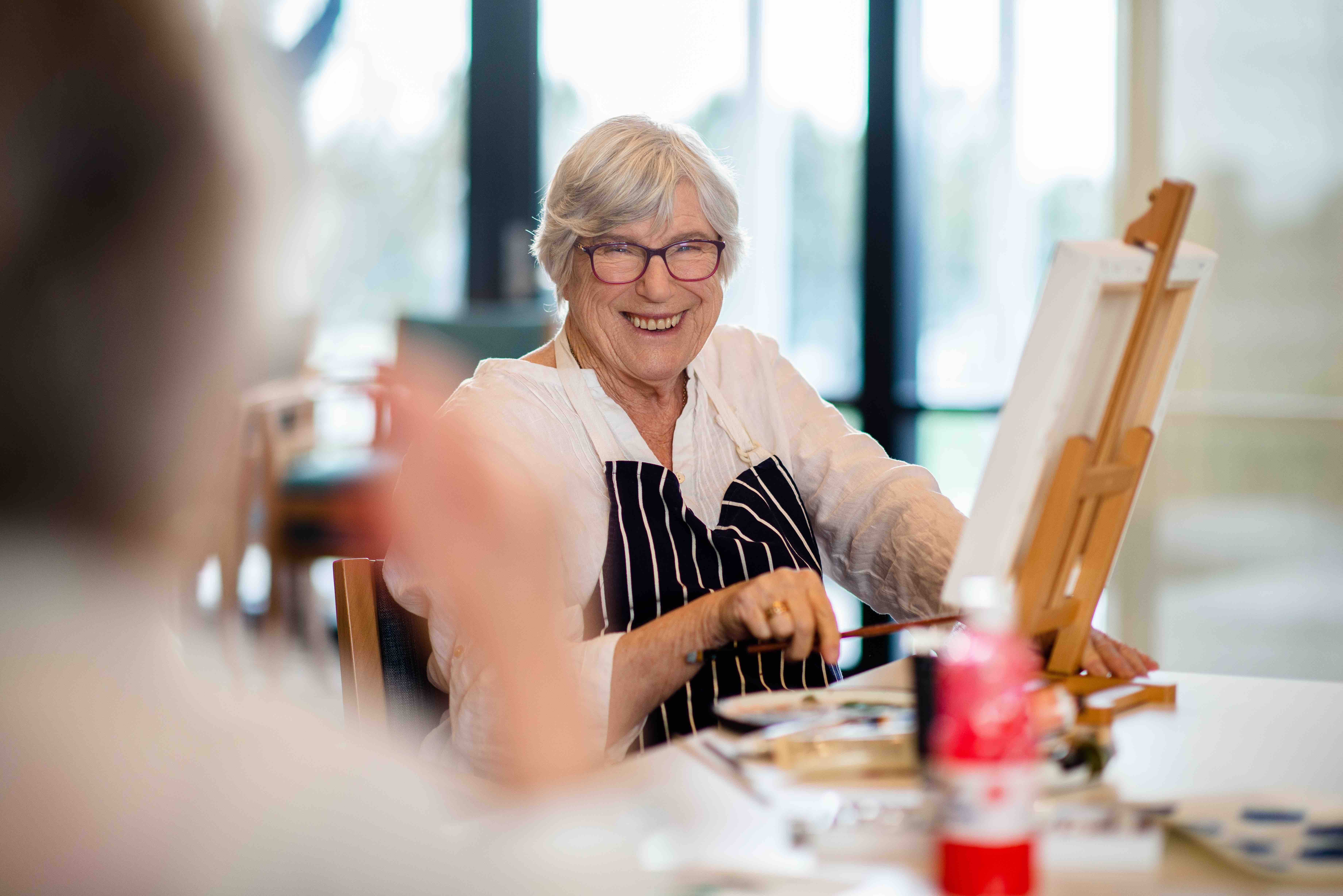 A smiling woman sits at a painting easel