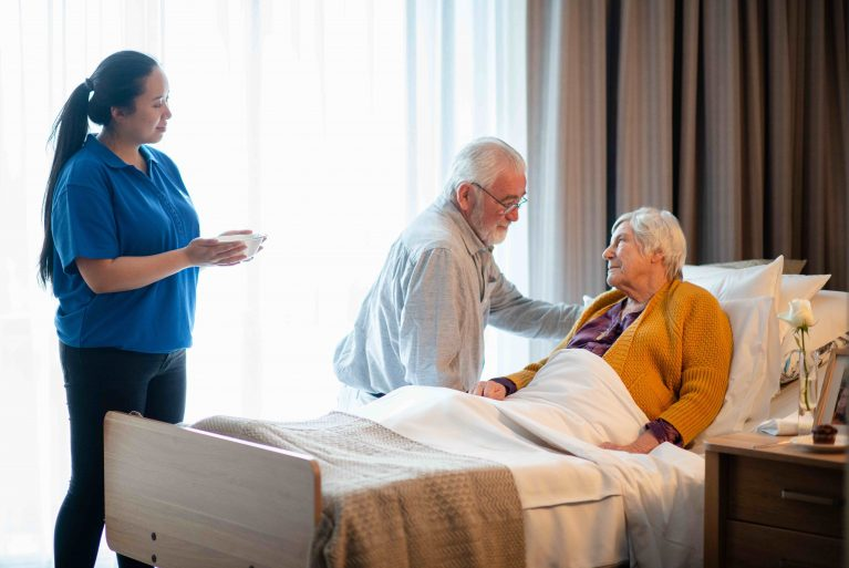 A woman is in a nursing home bed and a man sits at her side. A care worker looks on with a bowl of food for the woman.