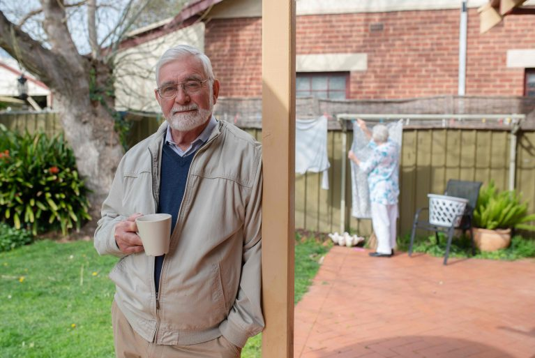 An older man, Richard, looks down the barrel of the camera with his wife struggling to hang out the washing in the background